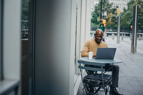 Concentrated African American male sitting at table and browsing laptop while working street cafe