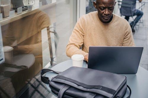Confident black entrepreneur with laptop in street cafe