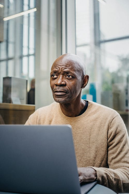 Pensive mature businessman working on laptop in cafe