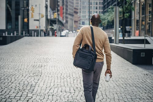 Black man walking on street with coffee and bag
