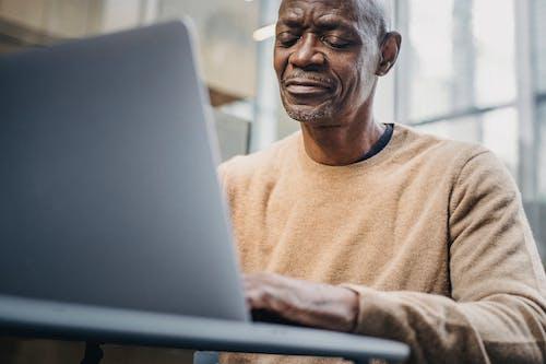 Mature businessman working on laptop in street