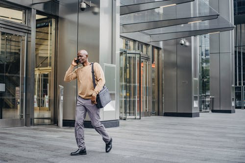 Elegant black entrepreneur walking and talking on phone