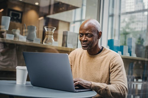 Smart African American man typing on netbook sitting at table with coffee cup against cafeteria window