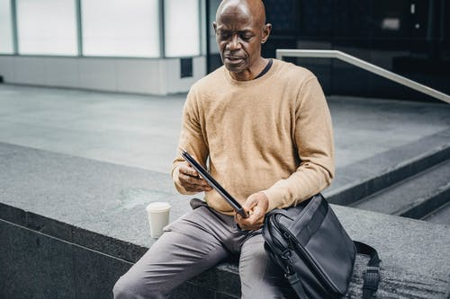 Mature black businessman with folder in street