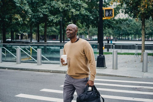 Mature African American man carrying disposable coffee cup and personal bag crossing street in downtown