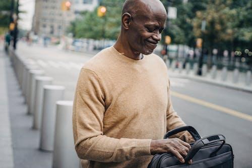Upset man opening case bag in downtown