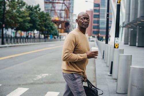 Formal black man with coffee on crosswalk