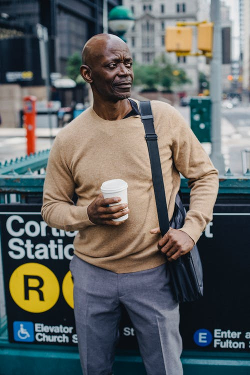 Black man standing near subway entrance with cup of coffee