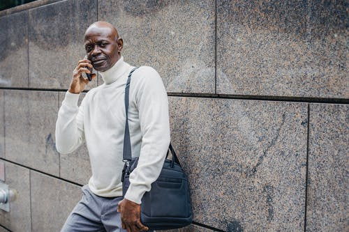 Serious middle aged African American male talking on smartphone and looking at camera while standing with bag on shoulder near marble wall