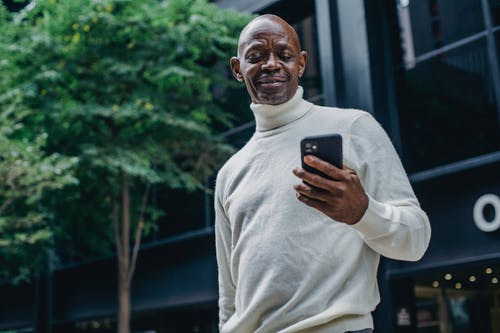 Cheerful black man browsing smartphone on street