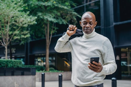 Confident African American male text messaging on smartphone while standing on street near tree with briefcase behind back in city