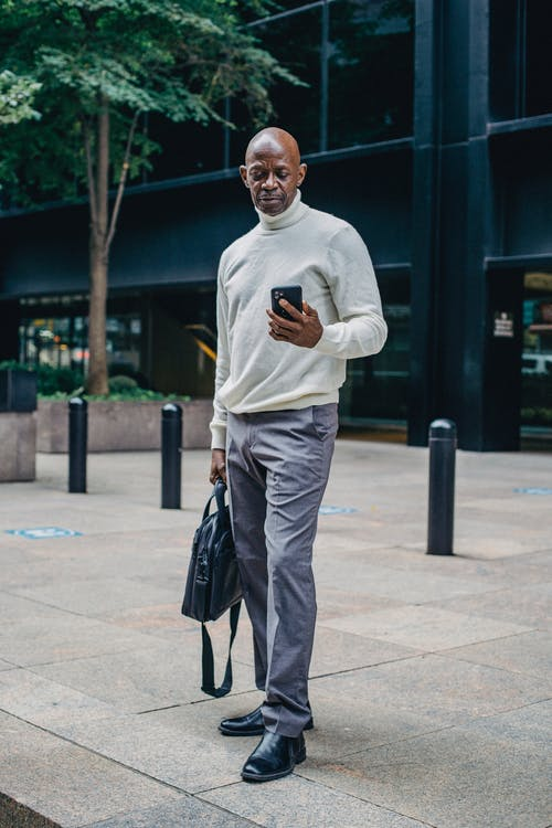 Busy black man with smartphone on street