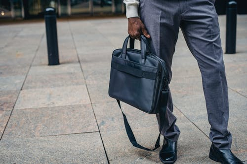 Crop faceless African American businessman in formal clothes with bag standing on pavement street