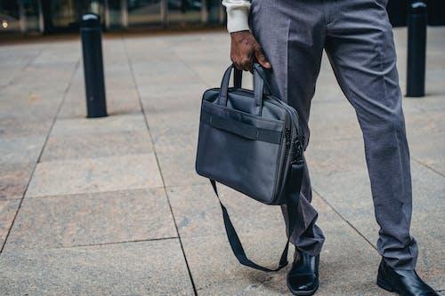 Crop man with bag on street