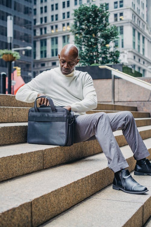 Black businessman sitting on stairs in city