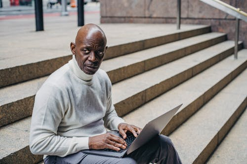 African American businessman in trendy outfit sitting on stairs and browsing laptop while working