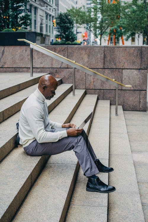 Black businessman with laptop on stairs