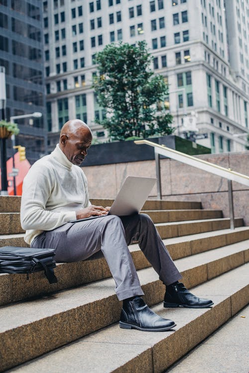Full body of African American man in formal wear sitting on stairs in downtown and browsing netbook during work