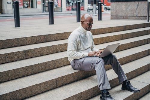 Black man working on laptop on steps
