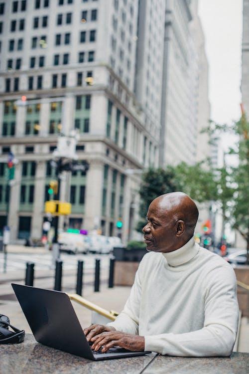 Black businessman with laptop on city street