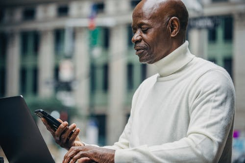 Side view of concentrated African American businessman in casual clothes browsing smartphone while working on laptop on city street