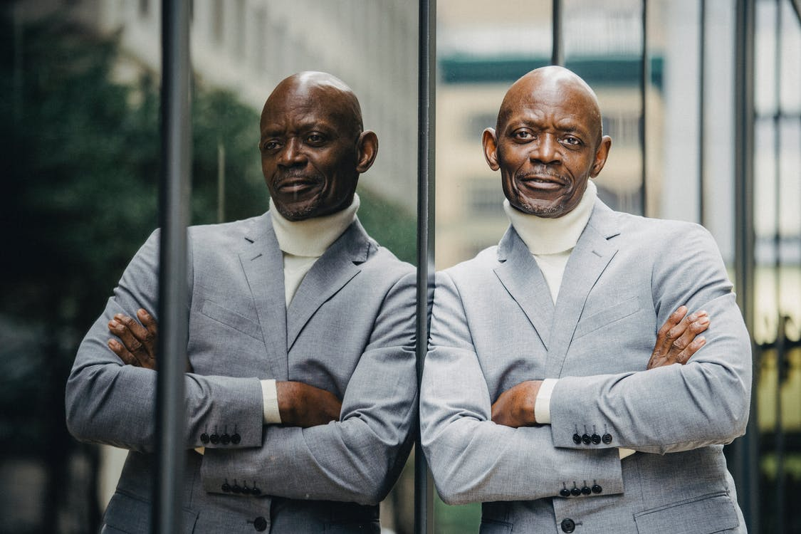 Serious black businessman leaning on glass wall