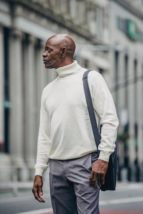 Black man standing on sidewalk of city