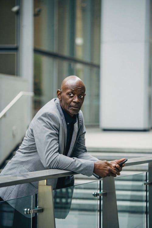 Confident African American businessman in formal suit leaning on glass railing and holding mobile phone while looking away