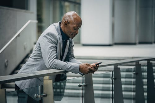 Black man browsing smartphone in business district