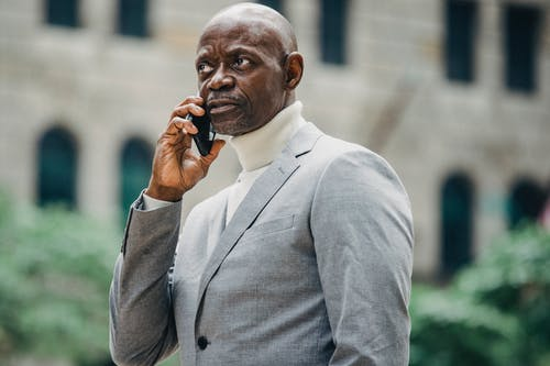Serious black businessman talking on mobile phone
