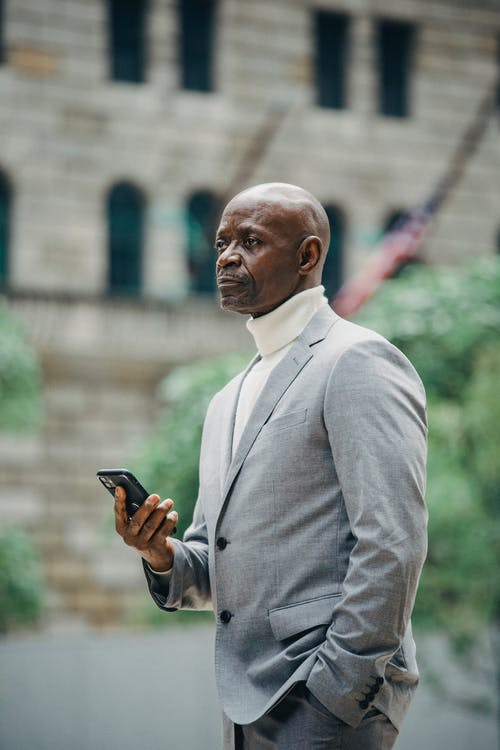 Black businessman with smartphone on street