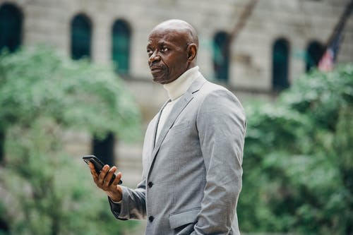 Side view of confident African American businessman in elegant suit standing on city street and using mobile phone while looking away