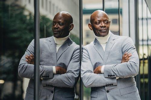 Selbstbewusster Schwarzer Mann, Der Sich Auf Glasgebäude Stützt