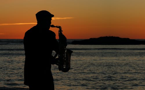 Silhouette of Man Playing Saxophone Near Body of Water during Sunset