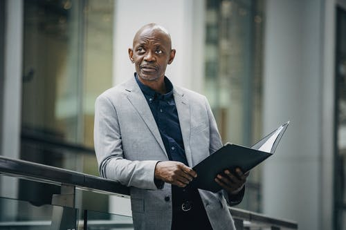 Confident African American manager in formal suit carrying folder with papers and looking away in soft daylight