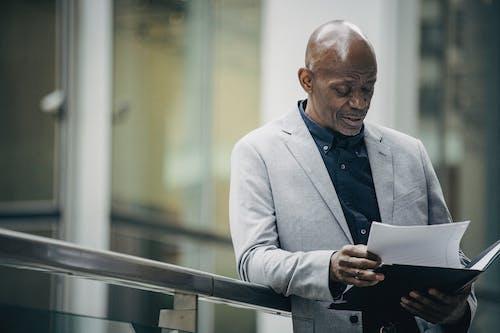 Konzentrierter Afroamerikanischer Unternehmer, Der Dokumente Auf Der Straße Liest