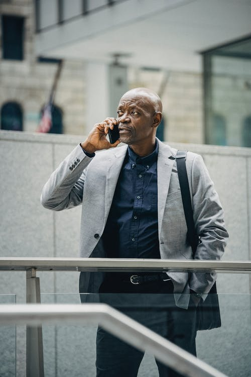 Busy black manager speaking on phone on street