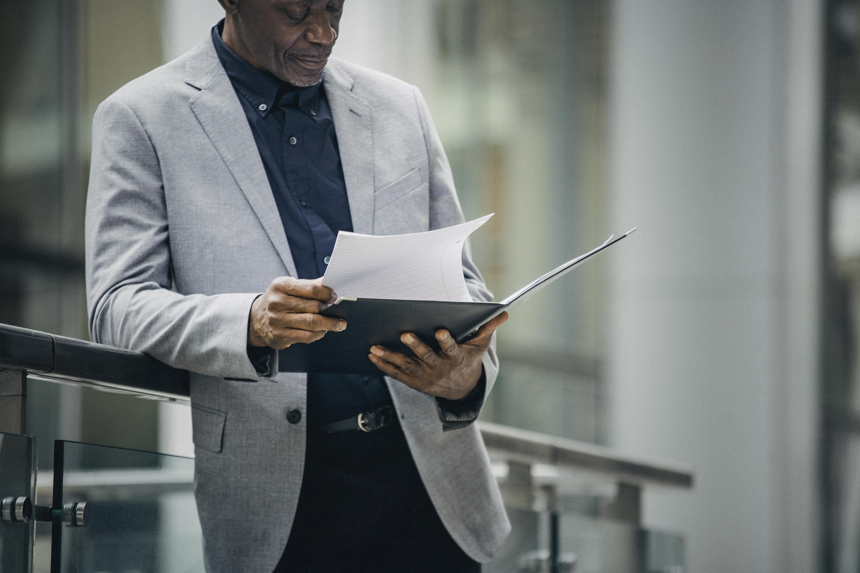 thoughtful black businessman analyzing documents on street