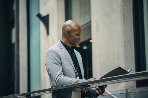 Cheerful African American manager reading documents in folder