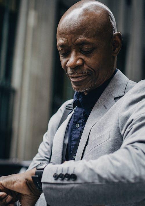 Confident black gentleman looking at wristwatch