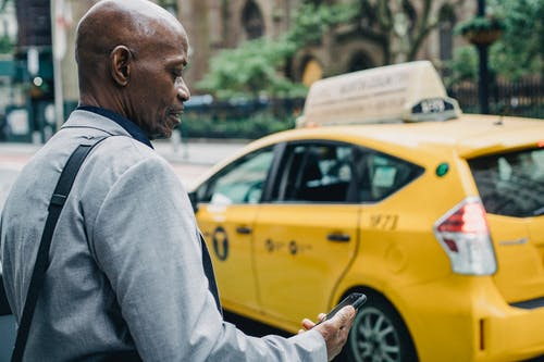Busy black businessman checking notification on smartphone while crossing street