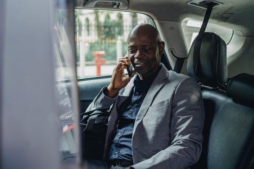 Content black man sitting in car and talking on smartphone