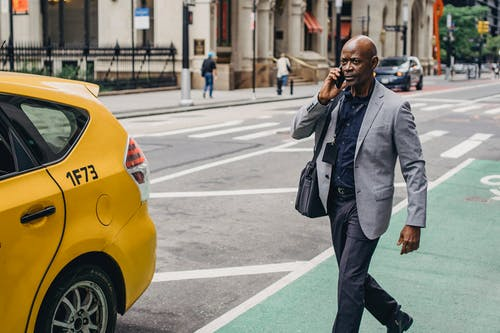 Thoughtful adult African American male in classy formal suit having phone call and walking towards taxi car parked on city street