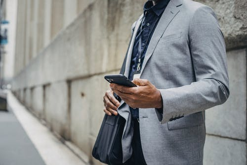 Crop unrecognizable African American male in formal suit standing on street and browsing modern mobile phone