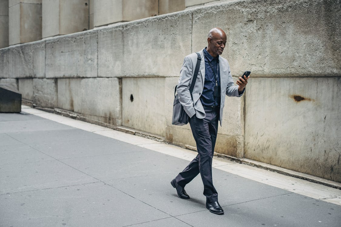 Full body content African American male in classy formal suit walking with hand in pocket along city sidewalk and browsing mobile phone