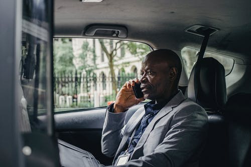 Serious black man speaking on smartphone in car
