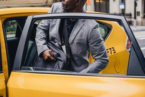 裁剪黑人男子坐在出租車停在街上