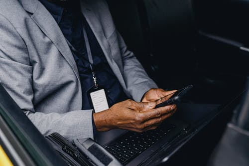 Crop faceless black businessman sitting in car and browsing smartphone