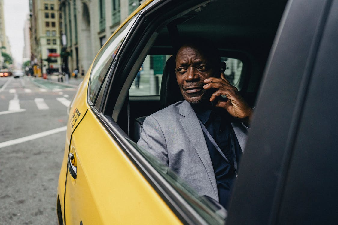 Serious African American male in formal clothes riding taxi on passenger seat and having conversation on mobile phone