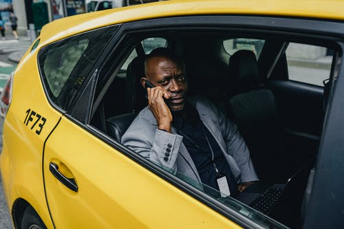 Pondering black businessman riding taxi and speaking on smartphone